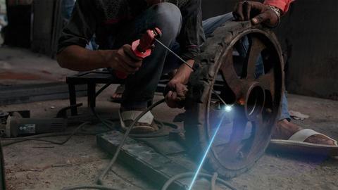 A boy welding cartwheel / bike's tyre in his workshop