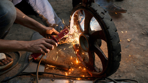 A boy welding a cartwheel tyre in his workshop along with the helpers