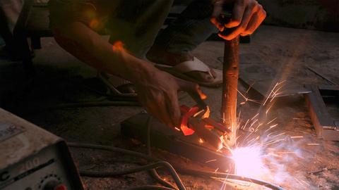 A man welding a metal block in his workshop