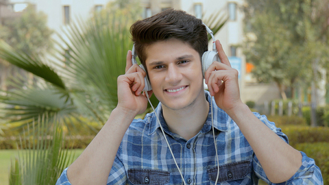 Young happy boy listening to music on headphones and singing outdoor