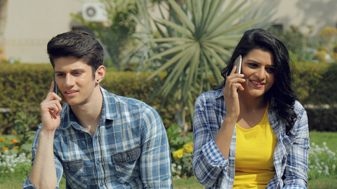 Mid shot of a young couple sitting together in a park talking on their cellphones