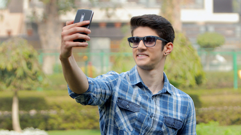 Young handsome boy wearing blue checks shirt and sunglasses taking selfies in a park on a bright sunny day
