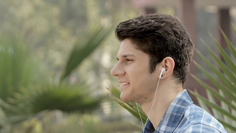 Close up of a boy in a park enjoying music on his earphones