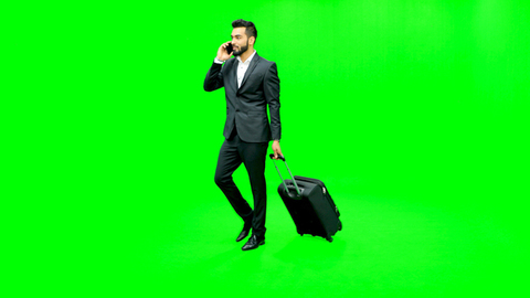 Young man dressed formally walking with a stroller and talking on his cell phone against the green screen