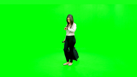Young girl in formals walking with a stroller and checking time on her wrist watch against the green screen