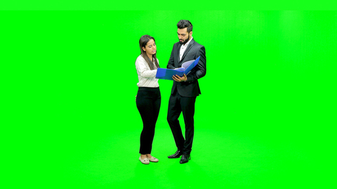 Professionally dressed young boy and girl discussing a file standing against the green screen