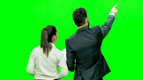 Formally dressed young boy and girl with file discussing against the green screen