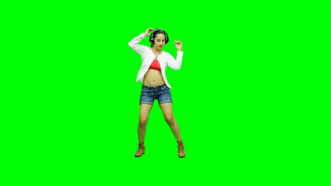 Full shot of a cute girl with headphones dancing against the green screen