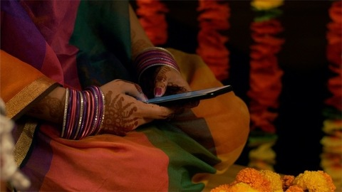 Woman with mehandi / henna tattoo on her hand texting on a smartphone