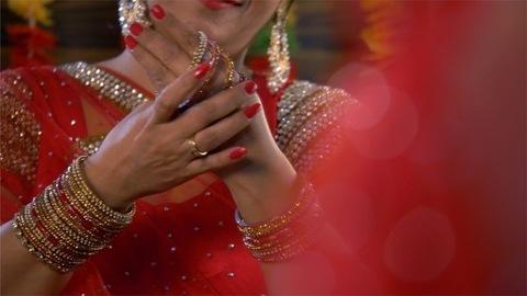 Beautiful Indian women in traditional dress putting on bangles / chudiyan