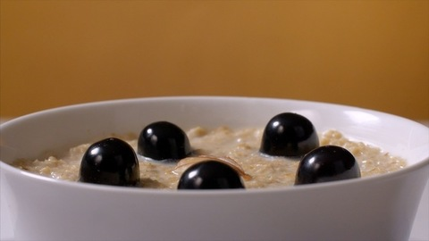 A bowl of oats with black grapes and sliced almonds rotating on a turntable