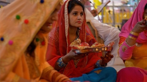 Indian married women doing Karwa Chauth Puja in traditional clothing at a temple