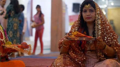 Beautiful Indian woman in traditional clothing performing Karwa Chauth rituals