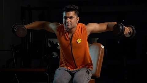 Indian male athlete performing shoulder training exercise while lifting weights