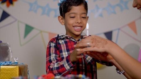 Mother teasing her son and feeding birthday cake - Boy wearing funny joker cap