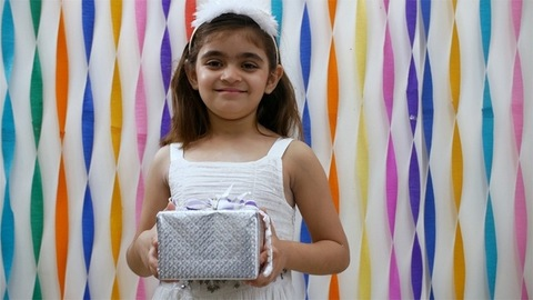 Portrait of smiling little girl holding a birthday gift in front of a decorated wall