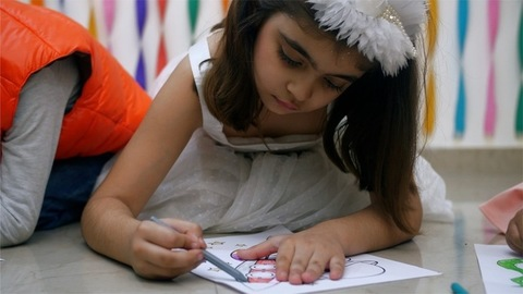 Calm and beautiful little girl coloring a sketch lying on the floor - Drawing competition amongst the kids