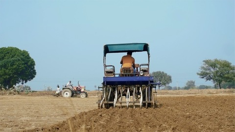 Stock video of a farmer driving a tractor for ploughing the field