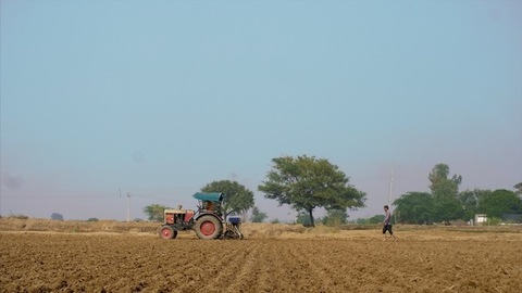 Indian Farmer plowing his field with the help of a red tractor - farming concept