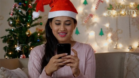 Close up of a young happy woman typing and chatting on her mobile phone with Christmas tree in the background