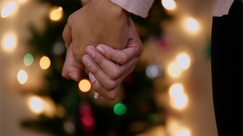 Closeup shot of a couple holding hands with Christmas tree in the background with bokeh effect