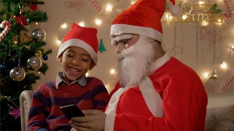 Happy little boy sitting on a couch with Santa Claus and watching a cartoon in the smartphone