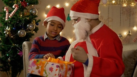 Young little boy sitting with Santa Claus and opening the Christmas gift
