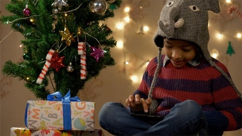 Boy wearing elephant cap playing with the smartphone near Christmas tree