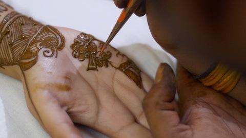 Mehndi artist applying beautiful henna / mehndi of the hands of an Indian bride