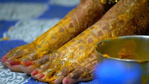 Closeup shot of Indian brides feet with mehndi and Haldi - pre-wedding ceremonies in India