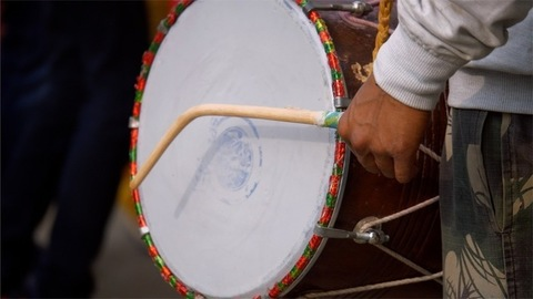 An Indian man playing dhol or drum during a baraat ceremony in an Indian wedding