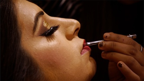 Closeup shot of a makeup artist applying lipstick to the bride on her wedding day