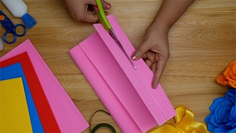 An Indian student cutting thin strips of paper for craft
