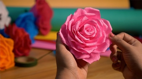 A closeup shot of pink rose made from paper by a kid in the art and craft class