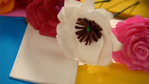Keeping white paper flower on the table among other crafted flowers
