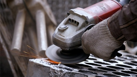 A worker wearing gloves smoothing the uneven metal block with grinding machine