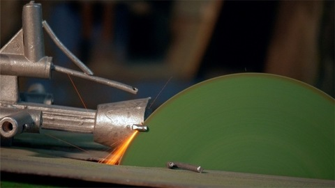 A worker in gloves cutting metal pieces with the grinder at the factory