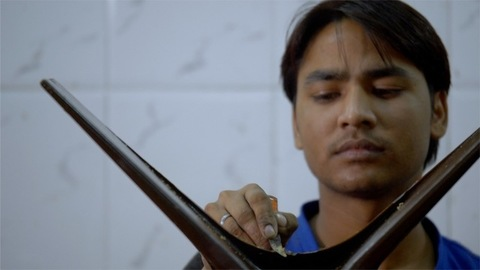 An Indian worker cleaning the metal surface with knife in an industry