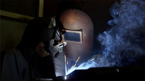 A worker welding at the metal factory in India
