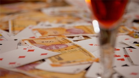 Shot of scattered deck of cards and Indian rupee banknotes