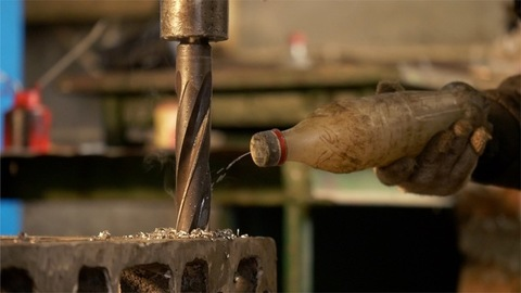 An industrial worker is putting water on a drilling machine tip to cool it off