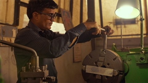 The worker working manually at lathe machine in workshop