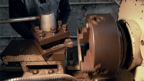 Shot of a worker working on a lathe machine