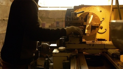 Hardworking worker operating the lathe machine in the plant