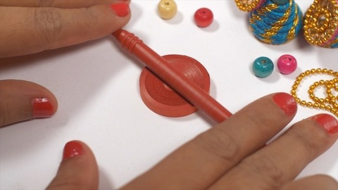A woman making handmade earrings using clay from home