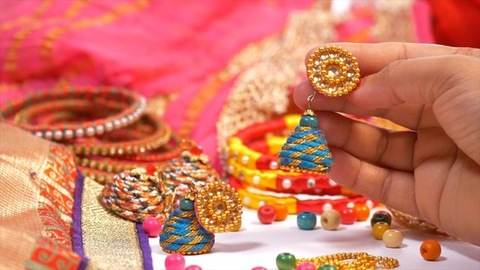 A young woman holding / checking a beautiful handmade earrings