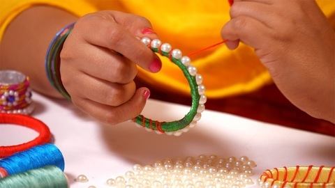Jewelry maker tying a colorful thread to keep the beads in a bangle intact