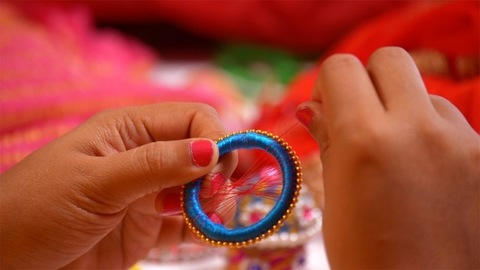 Professional jewelry designer putting a colorful thread around a bangle