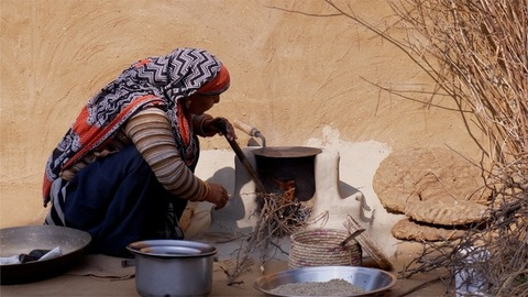 A rural Indian woman blowing into a chulha / traditional wood fire stove with a metal pipe