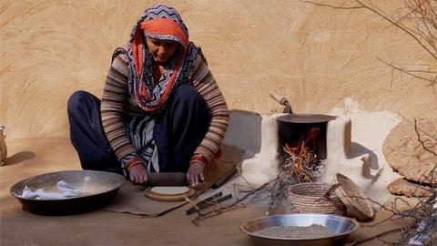 Desi Indian woman preparing roti / Indian bread in chulha for her family